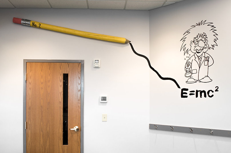 Intro to seventh and eighth grade slide: classroom art of Einstein with pencil writing on wall.