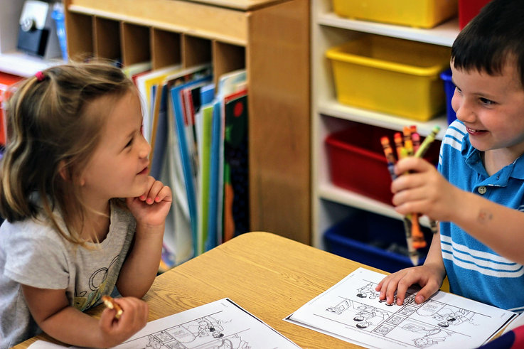 Young students learning learning and serving together.  Boy offers girl a handful of crayons.