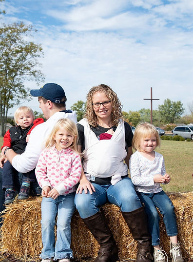 Kindergarten teacher, Mrs. Andrea Selves, with family & friends on hayride in front lawn of Beautiful Savior Lutheran Church.  Outdoor cross in background.
