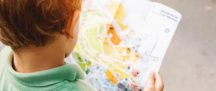 First & Second Grade Header Image: Young boy reading map.