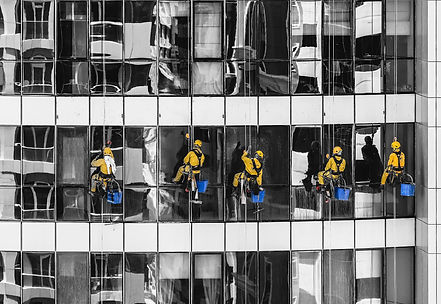 Cleaners cleaning glass window building.