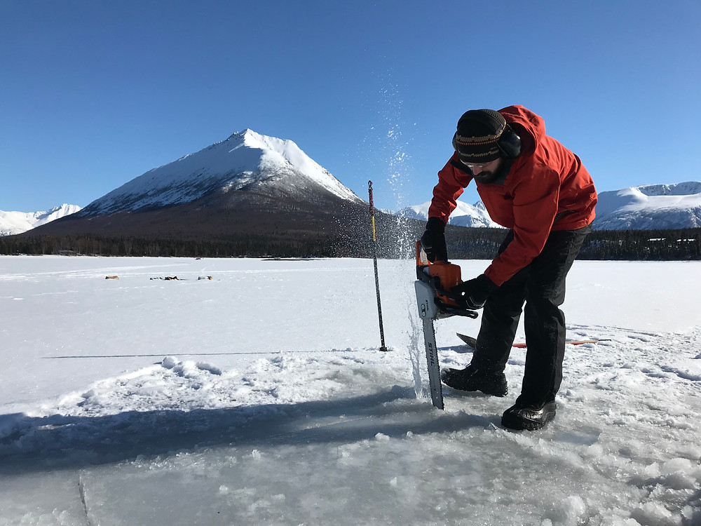 using a chainsaw to cut a hole in the ice for baptism