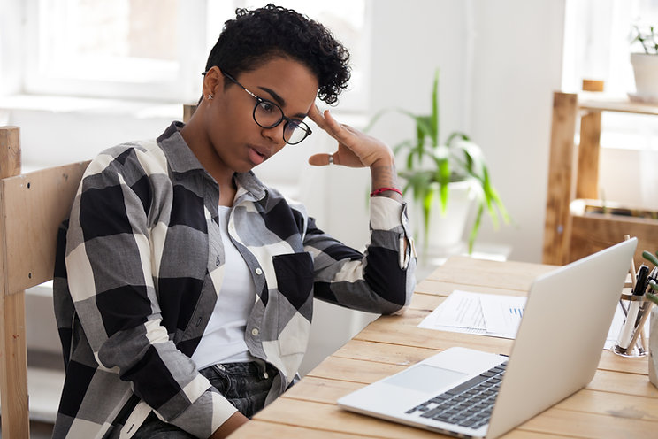 Frusturated Black woman sits at her computer. She learns more about starting a private practice from Private Practice Startup and downloading a free dream practice playbook