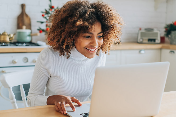 A woman smiles as she types on her laptop at the kitchen table. This could represent a private practice owner happy after finding a HIPAA form for her private practice paperwork. Contact us for free HIPAA compliance forms, private practice paperwork, and other services!