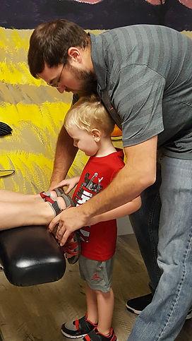 Kid helps with chiropractic adjustment.j