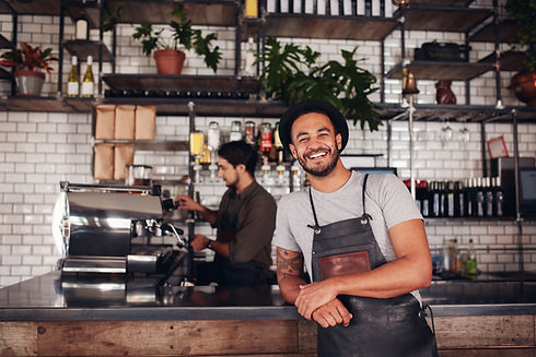 Coffee shop worker smiling to camera, st