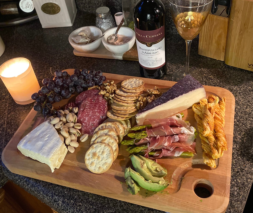 Charcuterie board with assorted Cheese, grapes and wine