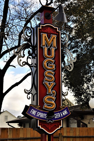 Mugsy's gold routed letters on red background pole sign with external overhead light.