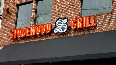 Studewood Grill open face channel letter wall sign is illuminated with exposed classic neon lights.