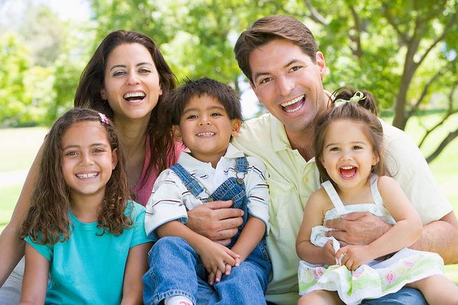 family-sitting-outdoors-smiling_HKlN7pCBi.jpg