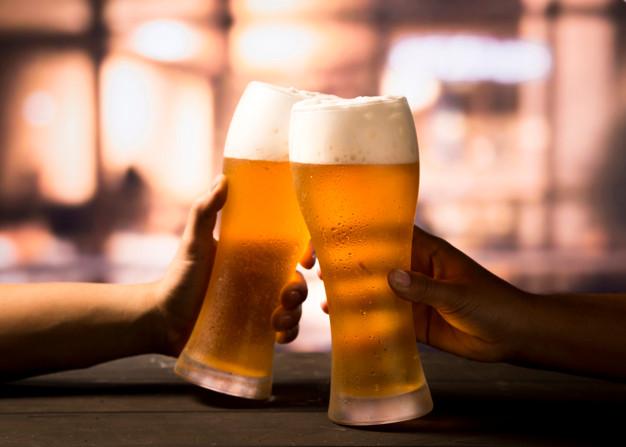 A imagem contém um brinde com cerveja