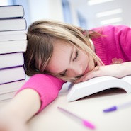 Student sleeping on desk in library around books