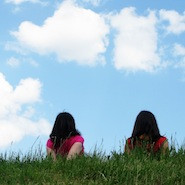 Two people looking at clouds in a field