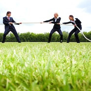 People in suits playing tug of war