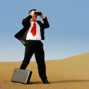Man in suit looking through binoculars