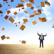 Man with books flying around him