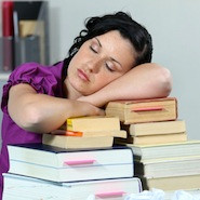 Woman sleeping on pile of books