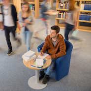 Student writing in a busy library