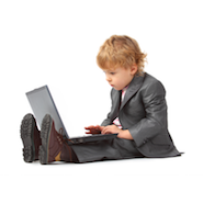 Little boy in a suit with a laptop