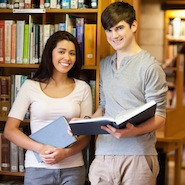 Two students smiling with books