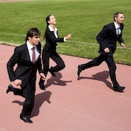 People running in suits on a track field