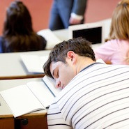 Male student sleeping at his desk