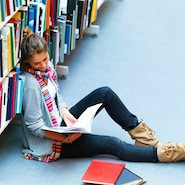 Student reading on library floor