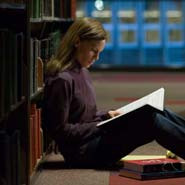 Woman sitting on library floor with a book