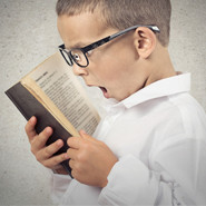 Surprised boy reading a book
