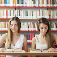 Two female students reading in library