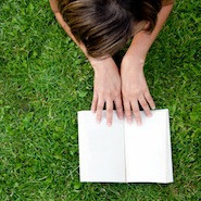 Girl reading book on the grass
