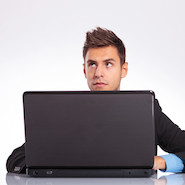 Pensive man in suit with laptop