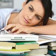 Girl laying head on pile of books