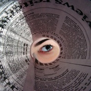 eye looking through a tunnel of newspaper