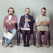 Three men sitting waiting for an interview