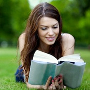 Woman reading outside on the grass