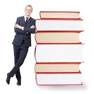 Man leaning against pile of books