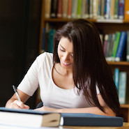 Student writing in a library