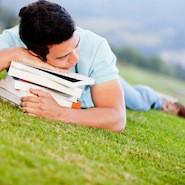 Student hugging books on grass