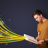Boy reading book with colourful lines flying out of it