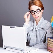 Woman in glasses looking at laptop screen