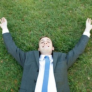 Man in a suit lying on the grass