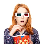 Woman eating popcorn in 3D glasses