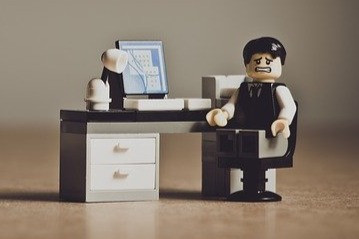 A well-dressed LEGO man with black hair, grimacing at the camera while sitting at a computer desk
