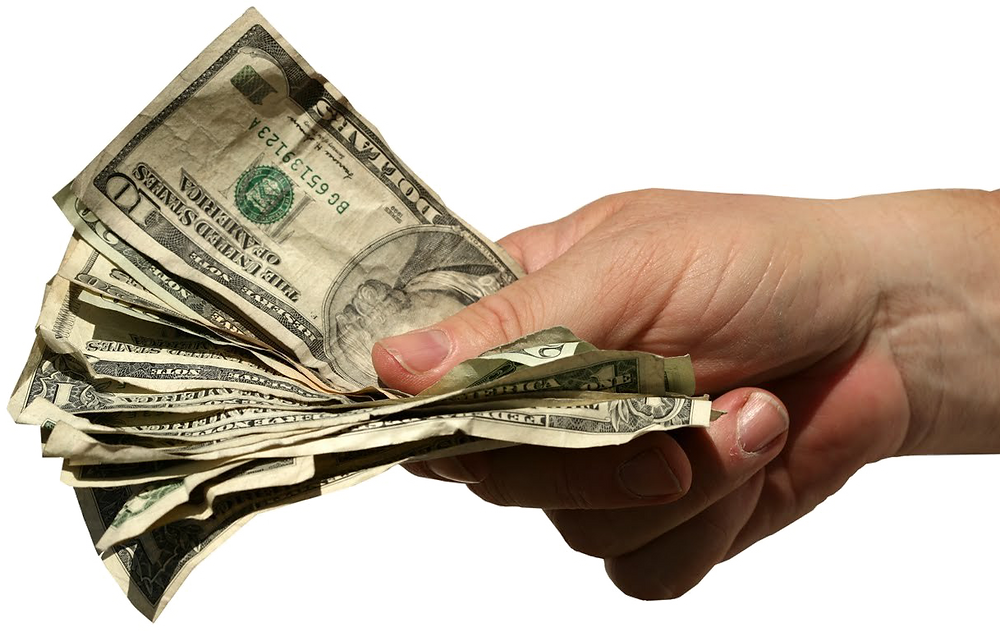 Grubby American money held out in a man's handGrubby American money held out in a man's hand