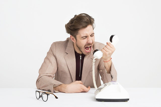 Man wearing brown suit jacket shouting into white telephone