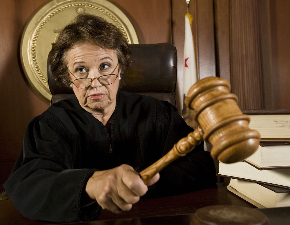 A middle aged female American judge in a courtroom about to strike her gavel.