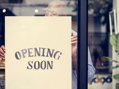 man-putting-on-store-opening-soon-sign-K