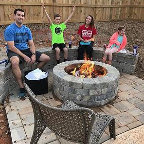 four peole sitting around a fire (landscap design)