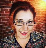 Krystal Iseminger, smiling, wearing glasses.